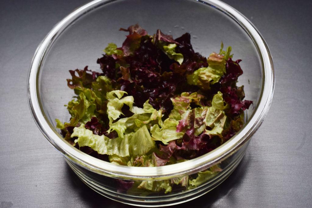 Salat in eine Schüssel geben